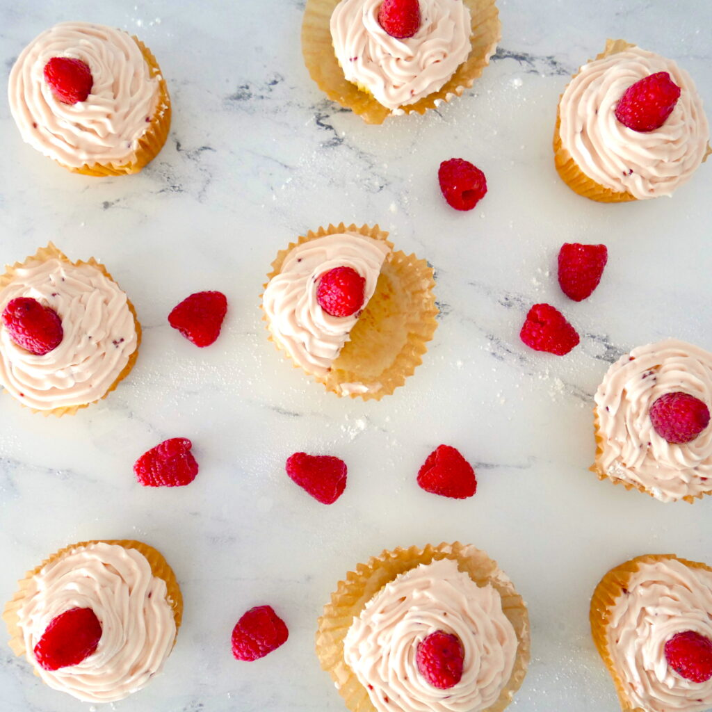 overhead shot of raspberry almond cupcakes in a formation on a white marble counter with raspberries scattered around