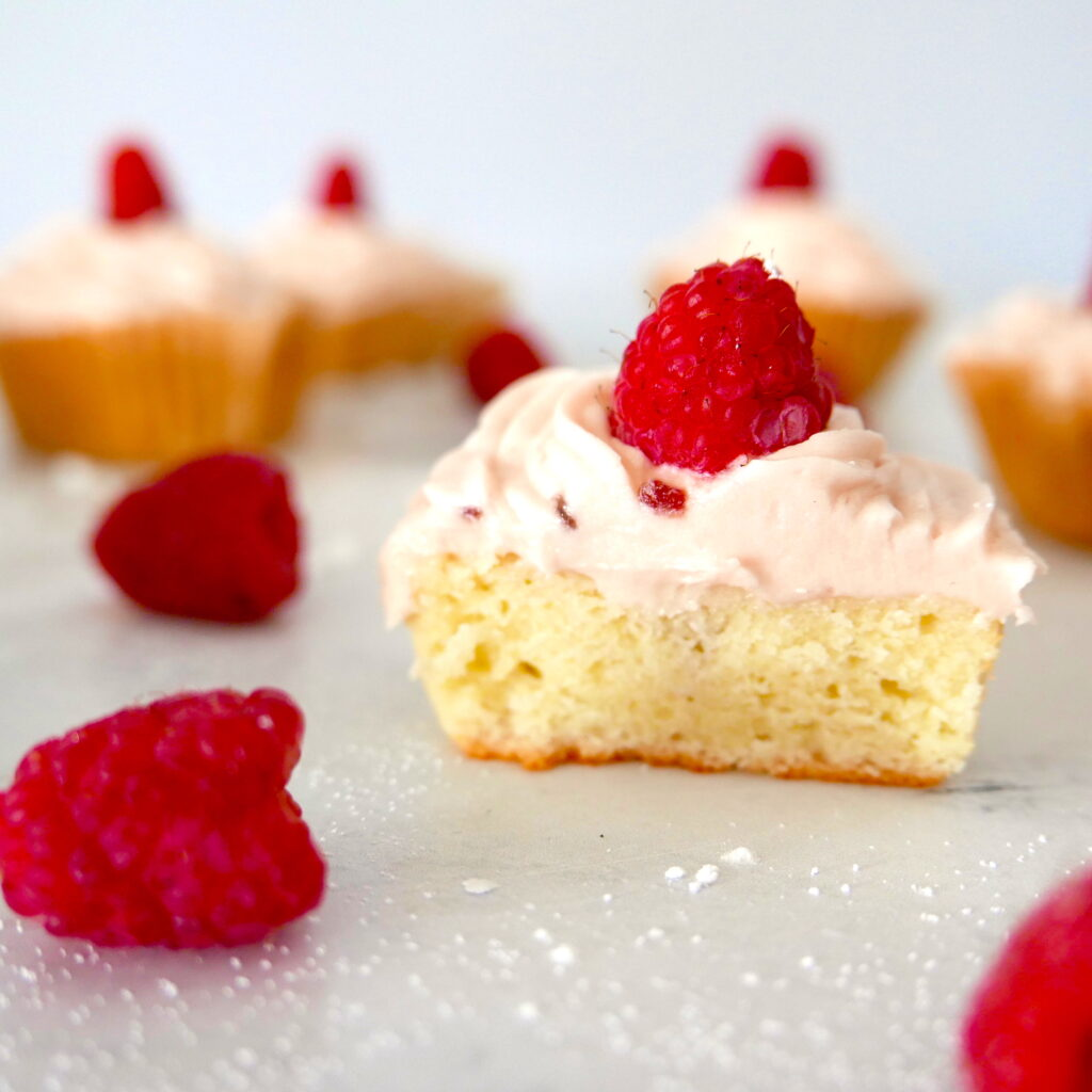 raspberry almond cupcake cut open with raspberry on top and more scattered around