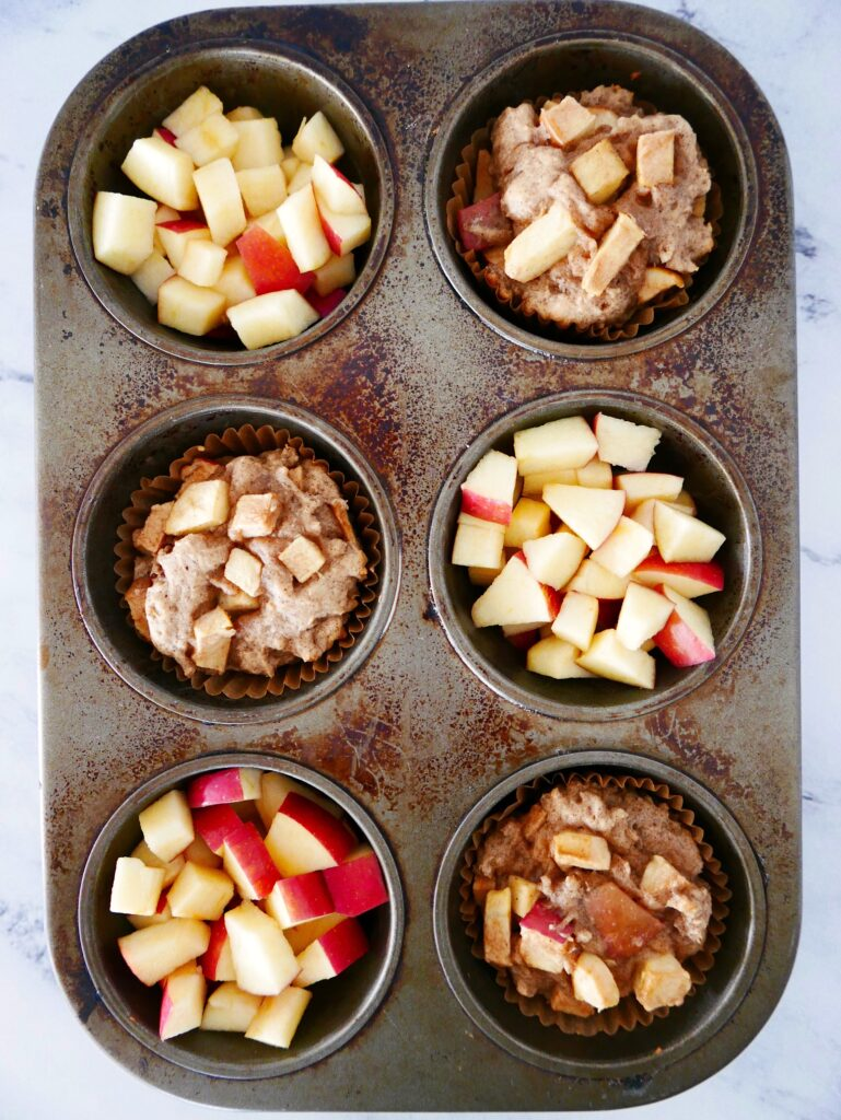 three gluten free apple muffins in a muffin tin with three of the cups filled with diced apples