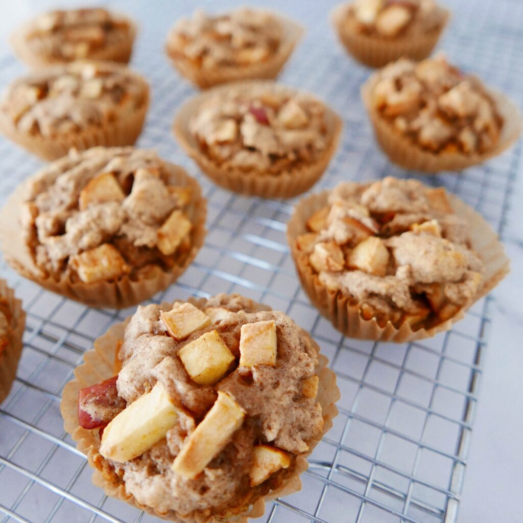 chunky gluten free apple muffins resting on a cooling rack
