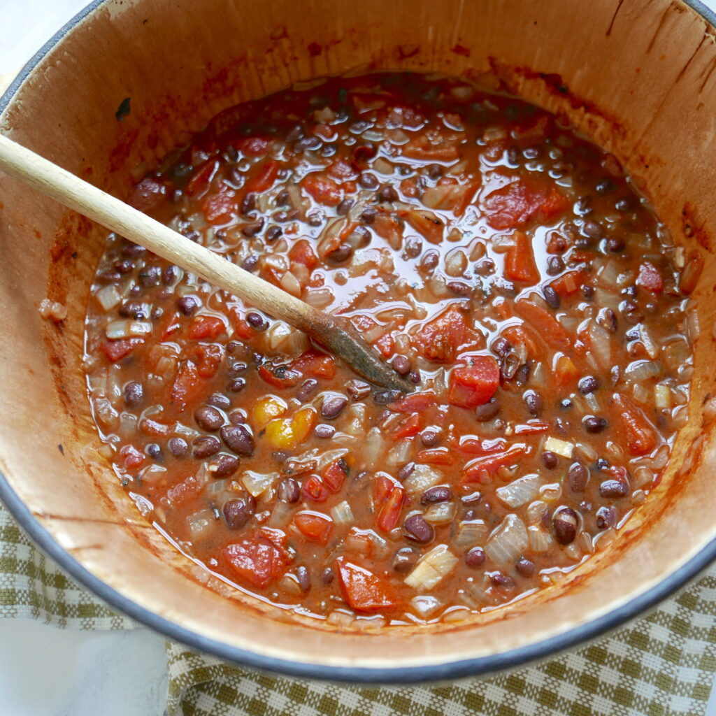 tomatoes, black beans, and onions being cooked in a large pot
