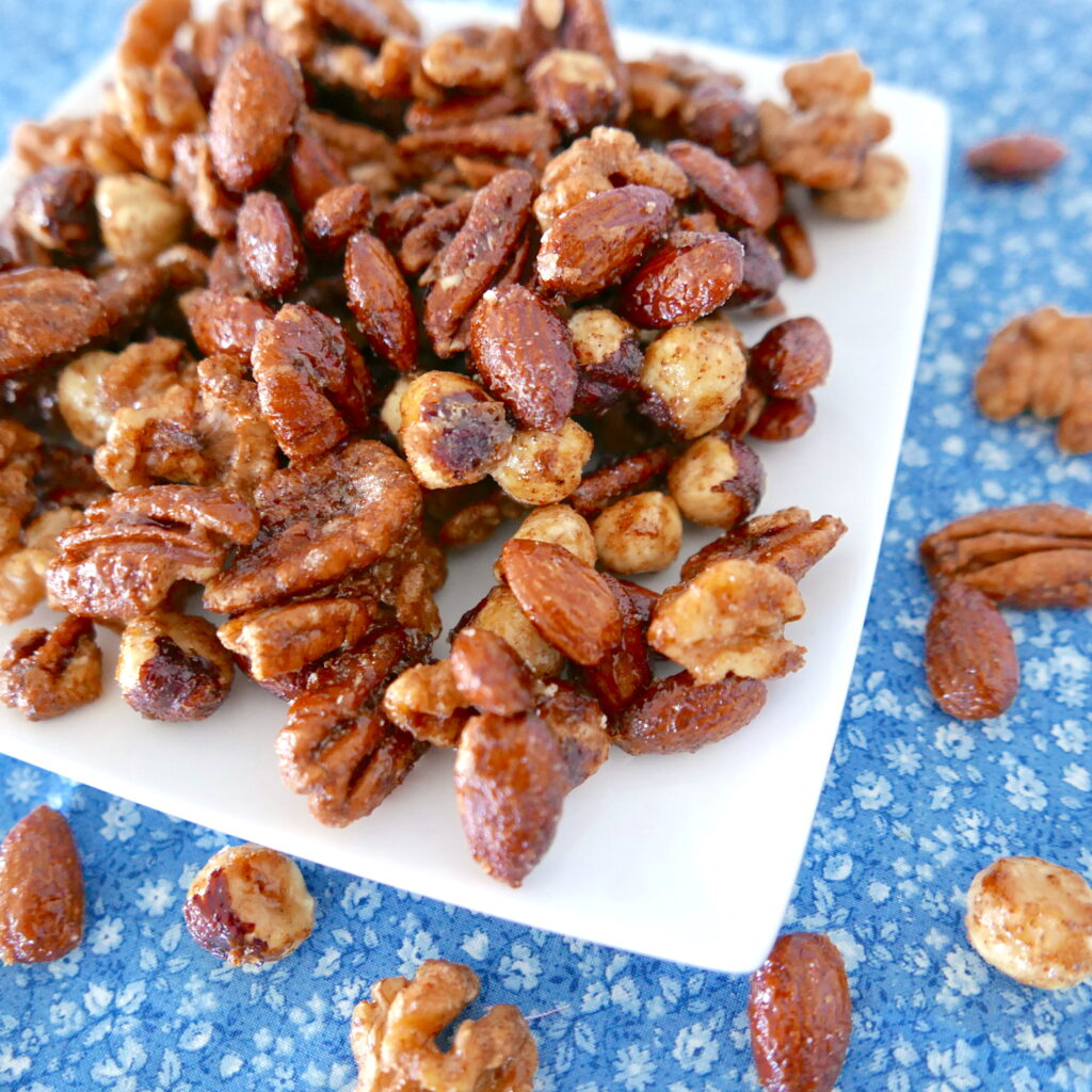 spiced candied mixed nuts arranged on a white plate with nuts scattered around on a blue tablecloth