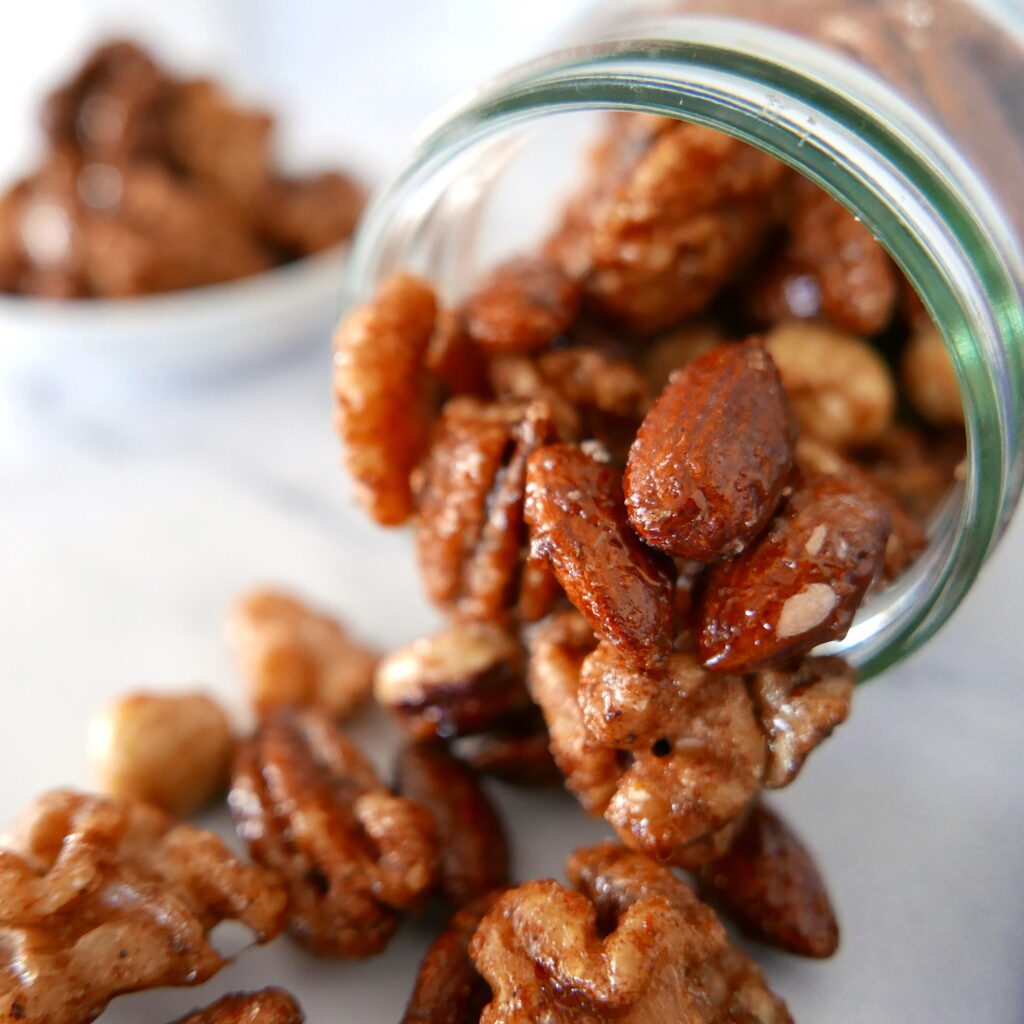 glass jar with mixed nuts spilling out of it onto a marble countertop