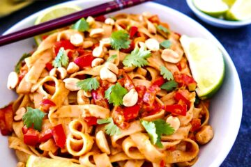 vegan peanut noodles with lime and chopsticks on a white plate