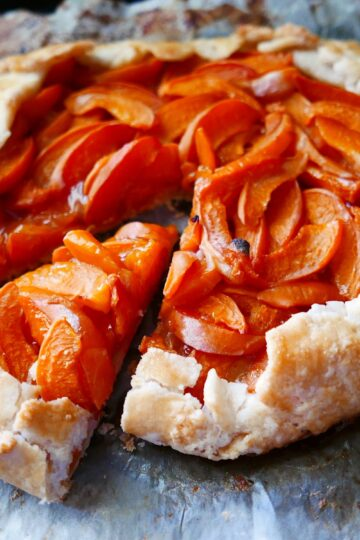 apricot gluten free galette on a baking sheet with one piece cut