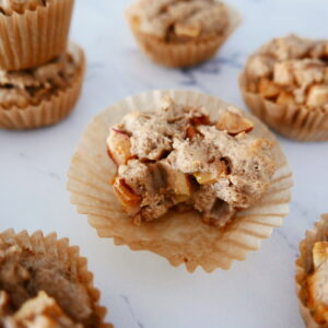 chunky gluten free apple muffins arranged in a pattern on a white marble counter