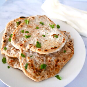 sourdough naan garnished with cilantro on a white plate with white napkin underneath