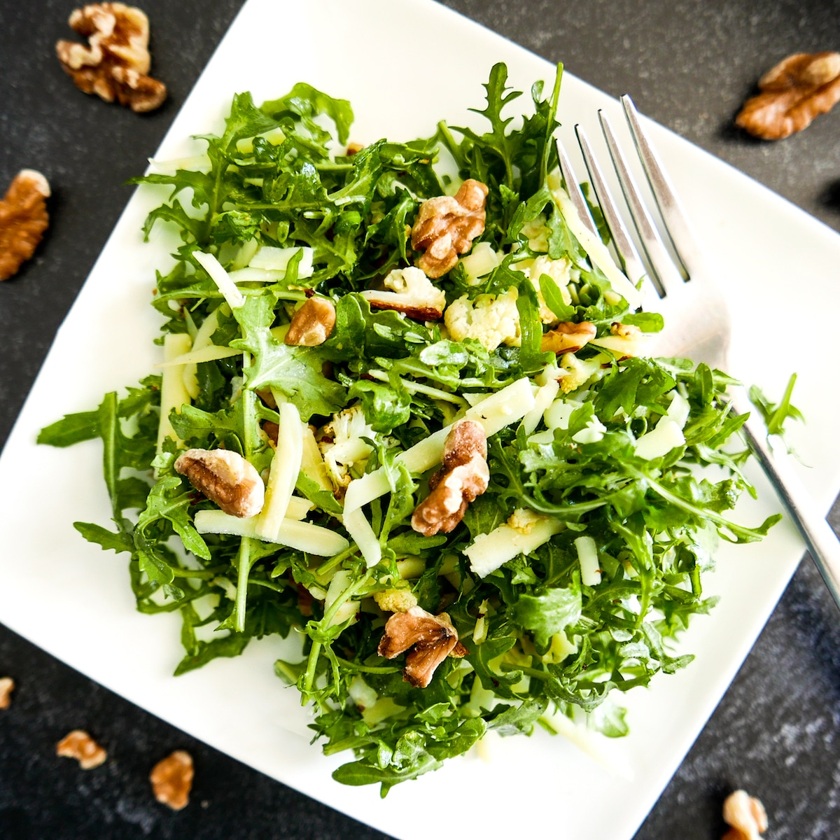 cauliflower salad with walnuts on a white plate with fork and walnuts scattered around