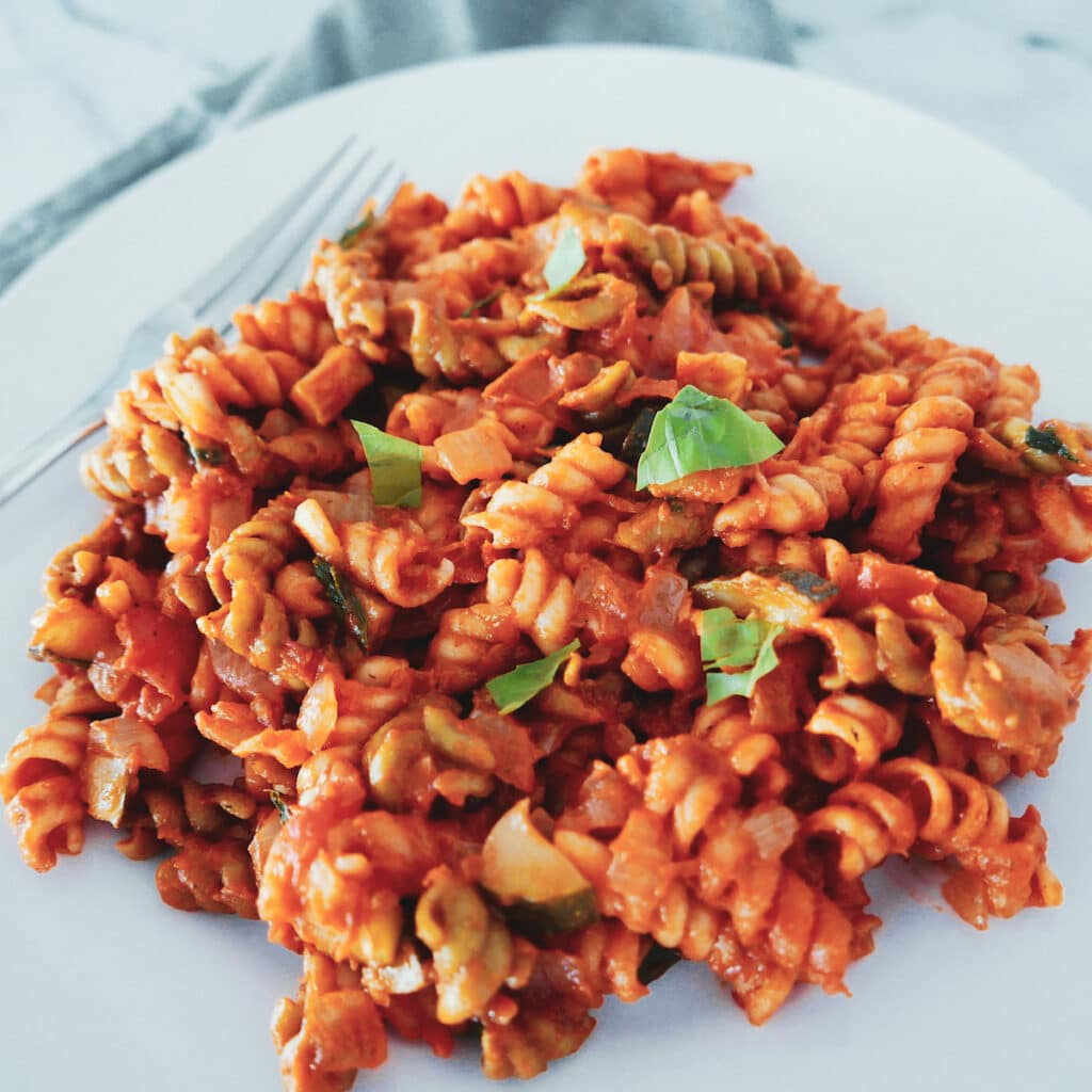 one pot pasta with tomato mascarpone sauce on a white plate with basil