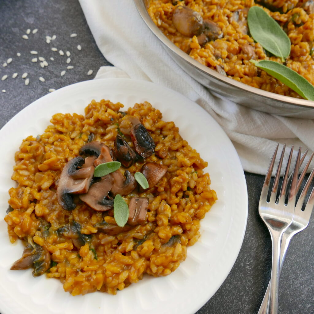 pumpkin risotto on a white plate with two forks and a pan of risotto in background