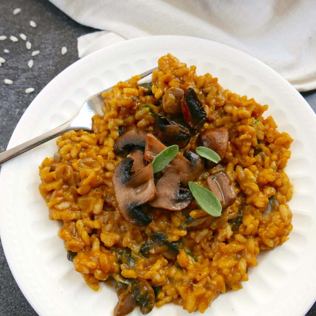 pumpkin and mushroom risotto garnished with mushrooms and sage on a white plate with fork and a white napkin in background