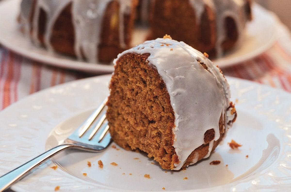 pumpkin spice bundt cake slice on a white plate with fork