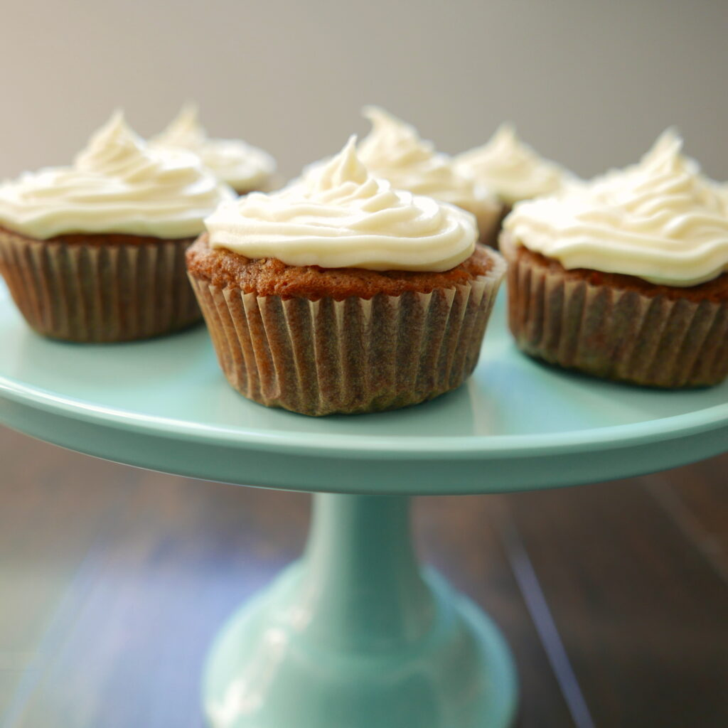 carrot cake cupcakes displayed on a teal cake stand