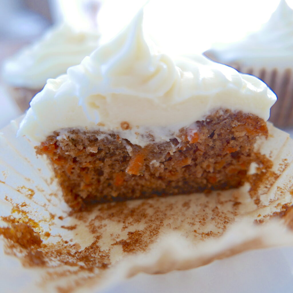 carrot cupcake cut in half on a white plate
