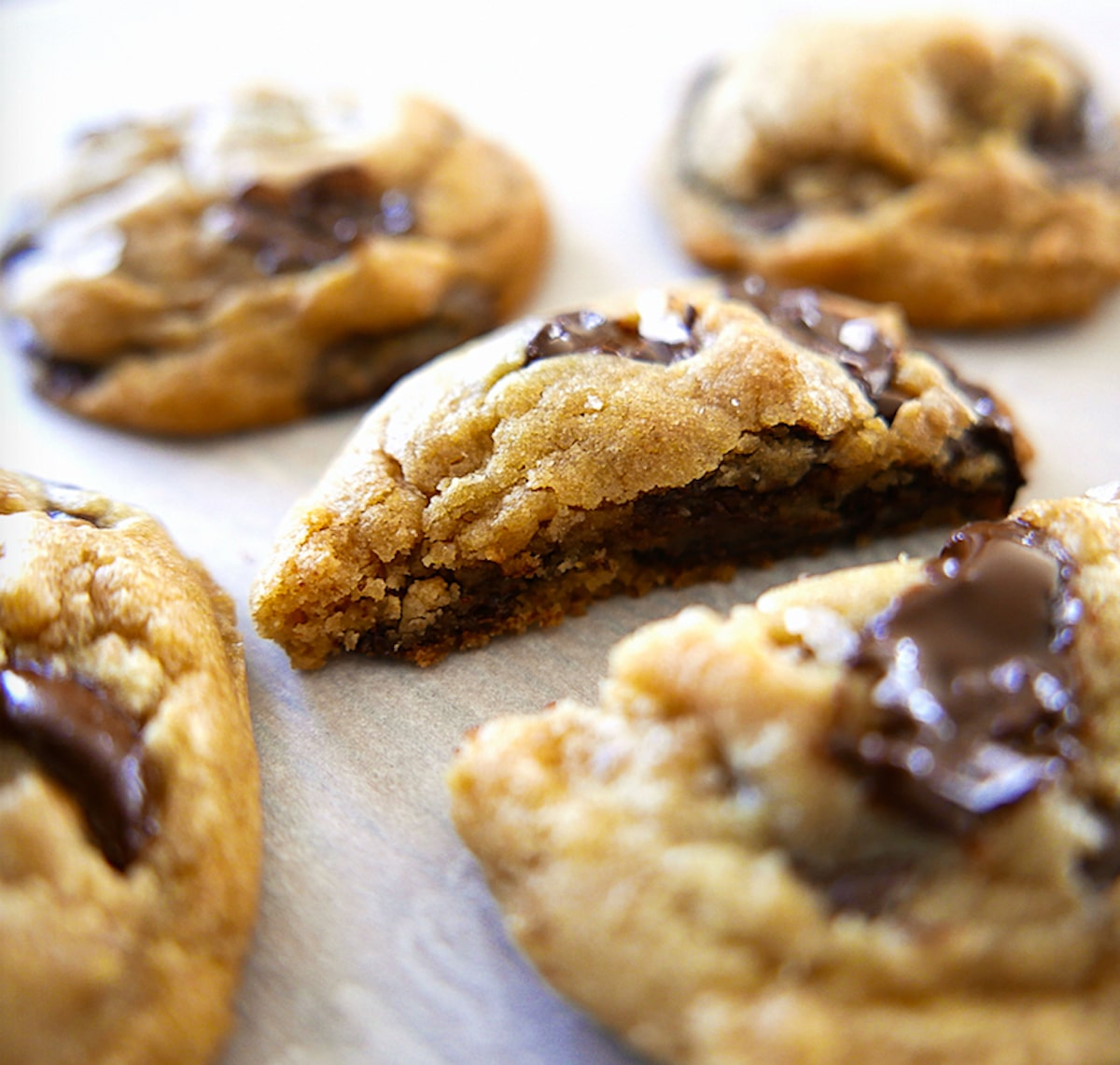 close up of inside of brown butter chocolate chip cookie on parchment paper