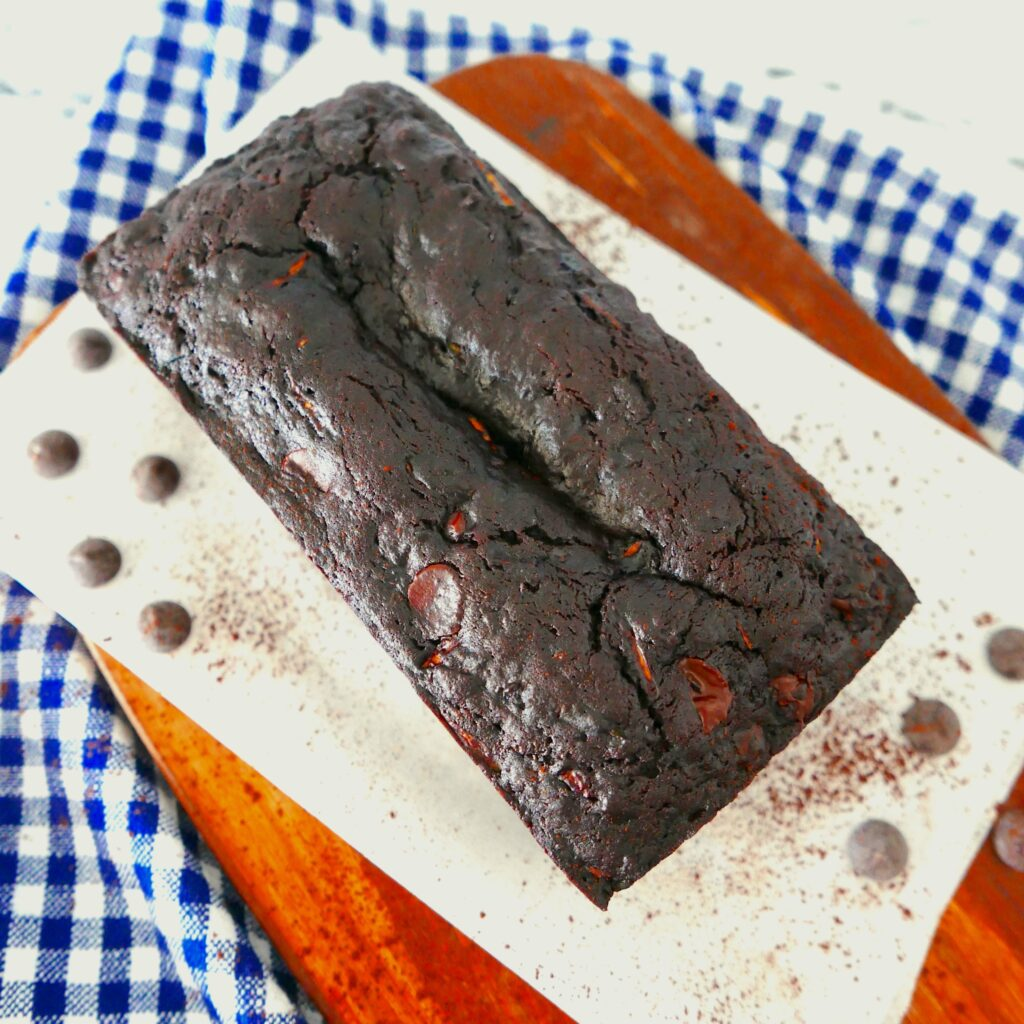 chocolate zucchini loaf resting on a wooden cutting board with parchment paper
