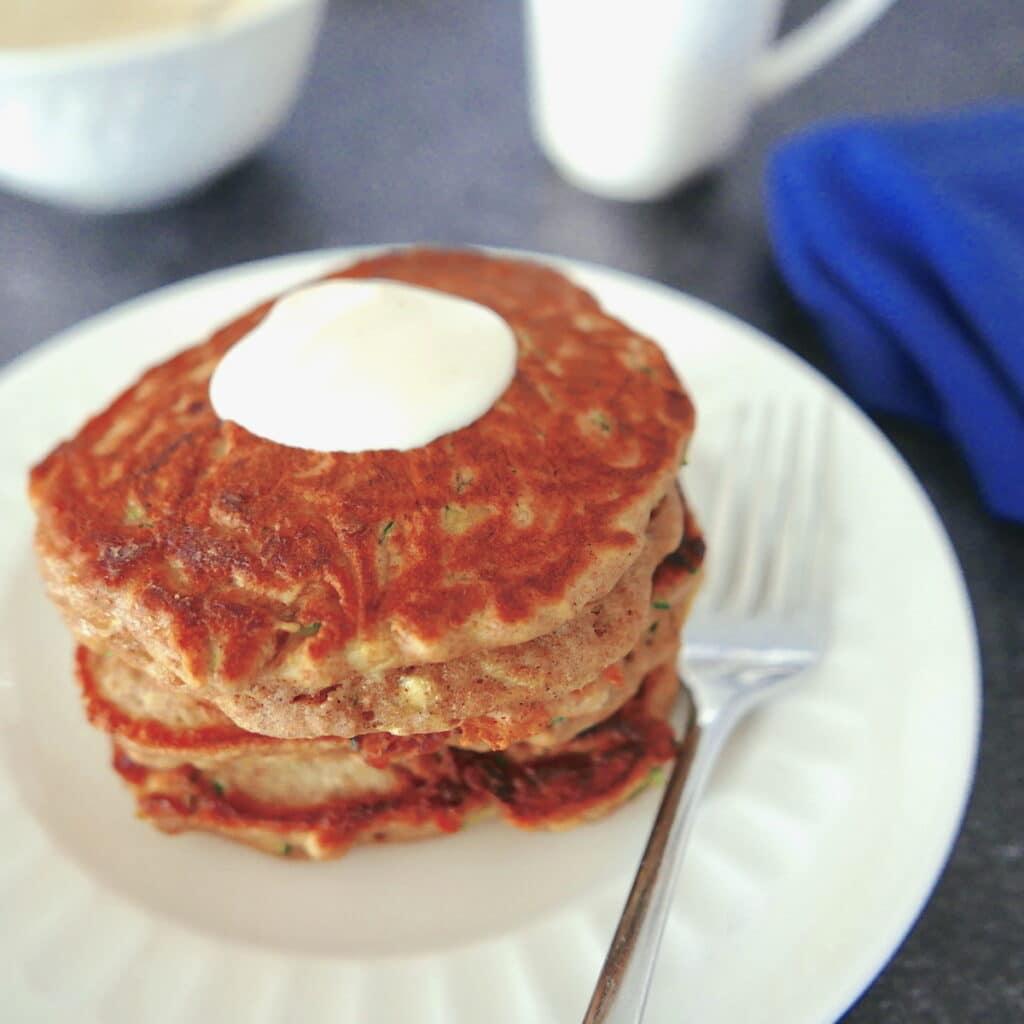 zucchini bread pancakes on a white plate with fork with white coffee cup in background