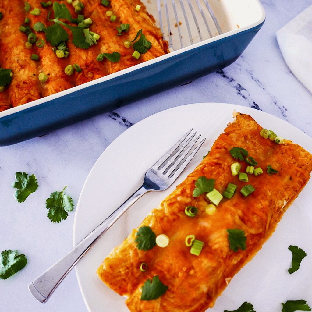 two chipotle chicken enchiladas on a white plate with fork