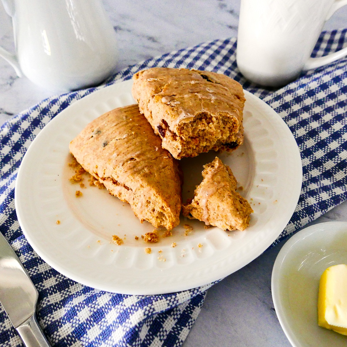 two cinnamon raisin scones on a white plate with piece broken off and resting on a plaid napkin