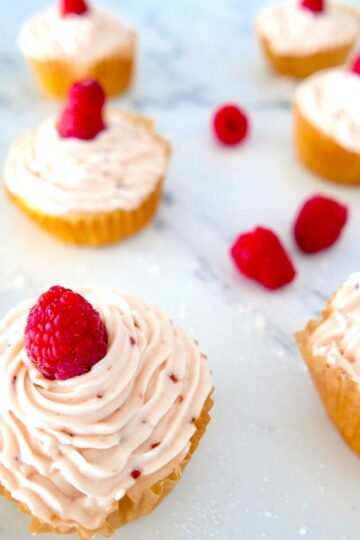 raspberry almond cupcakes arranged on a marble counter top with fresh raspberries
