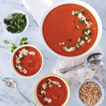 butternut squash carrot ginger soup in three bowls with spoons
