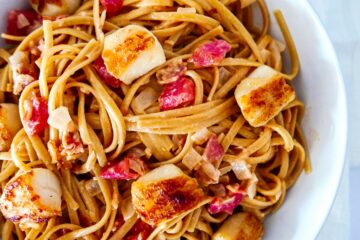 pasta with scallops and bacon in a white bowl