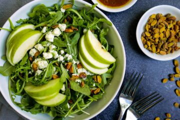 harvest apple salad in white bowl with two forks and pistachios in a cup