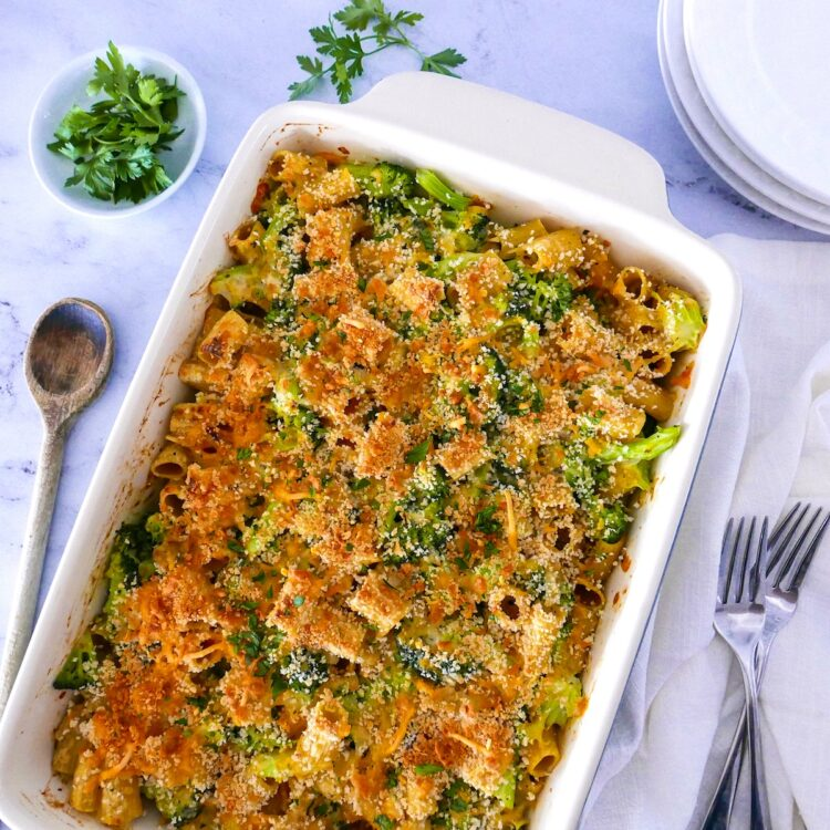 broccoli pasta bake with plates, parsley, serving spoon, and napkin