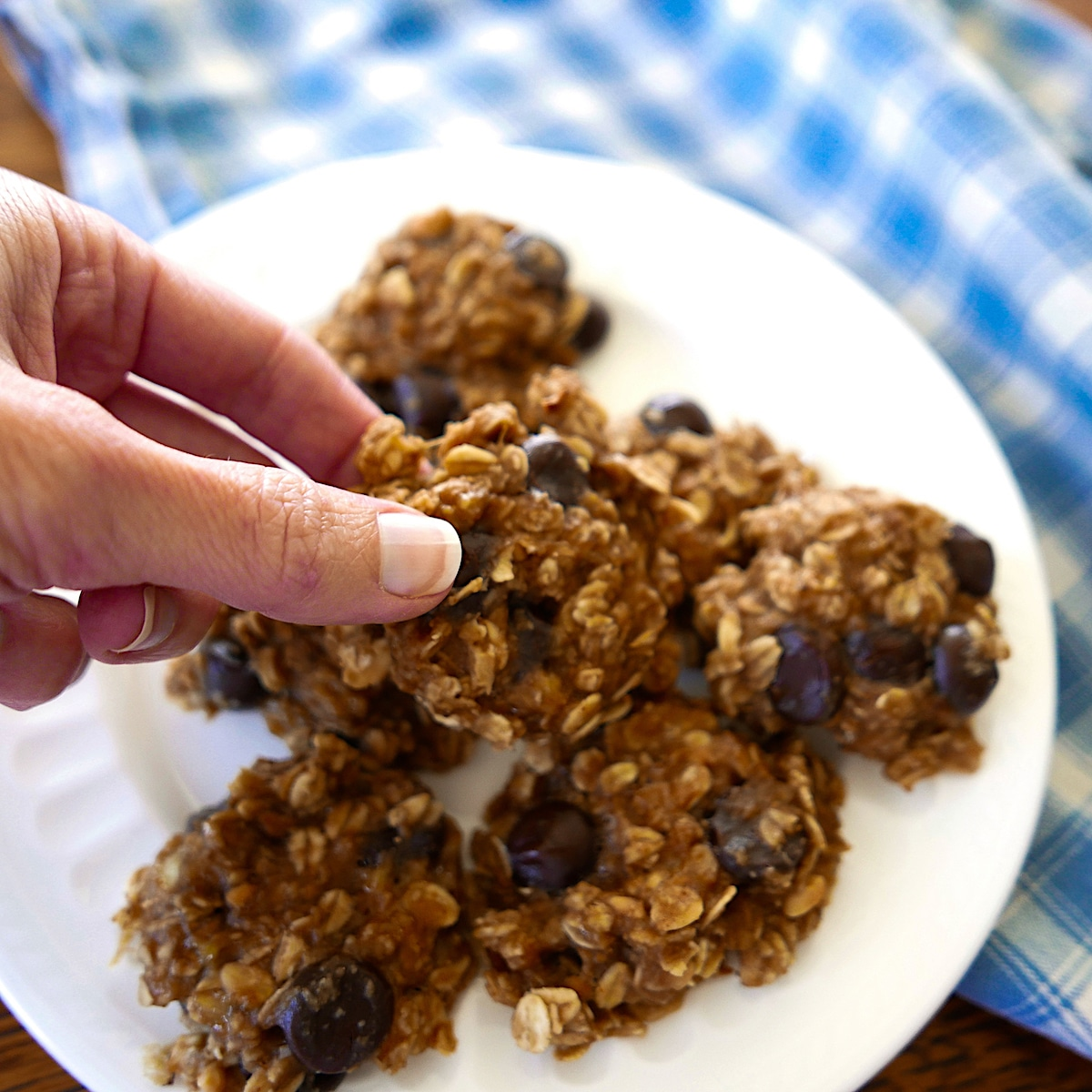 peanut butter banana oatmeal cookies on a white plate with hand picking up one cookie