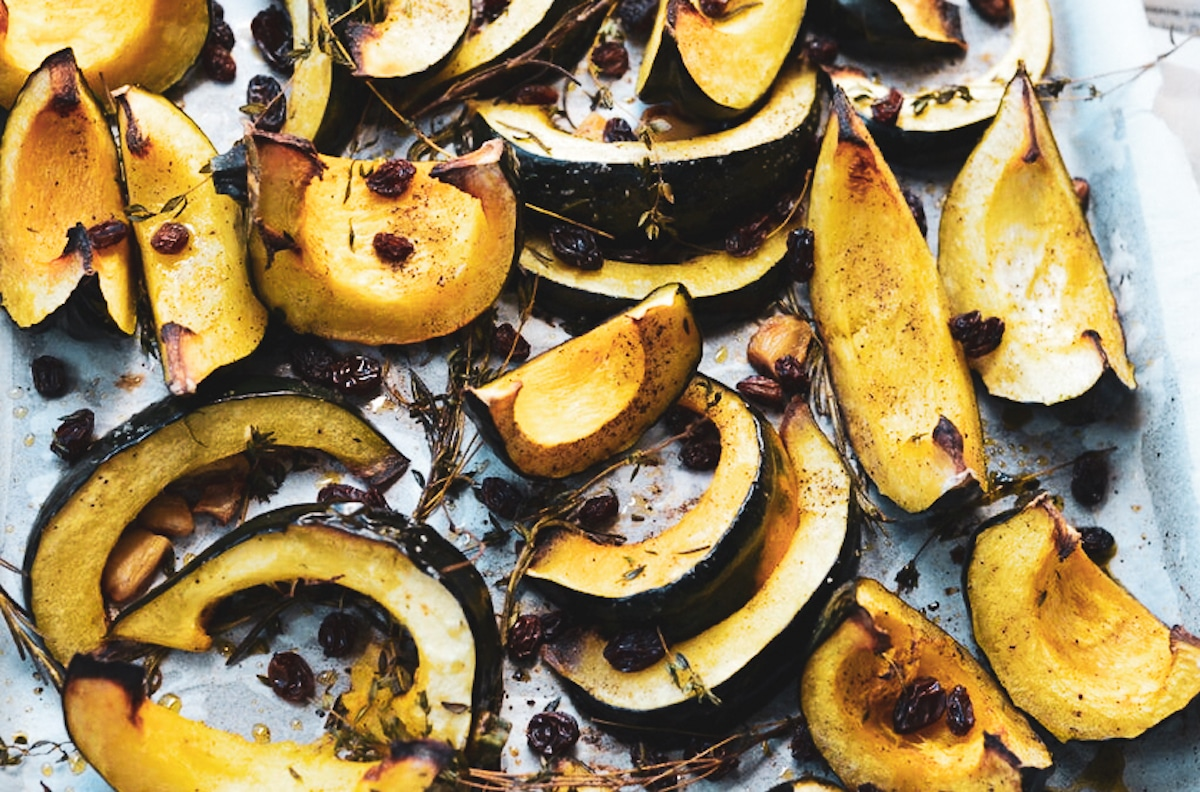 acorn squash wedges with thyme on a baking sheet