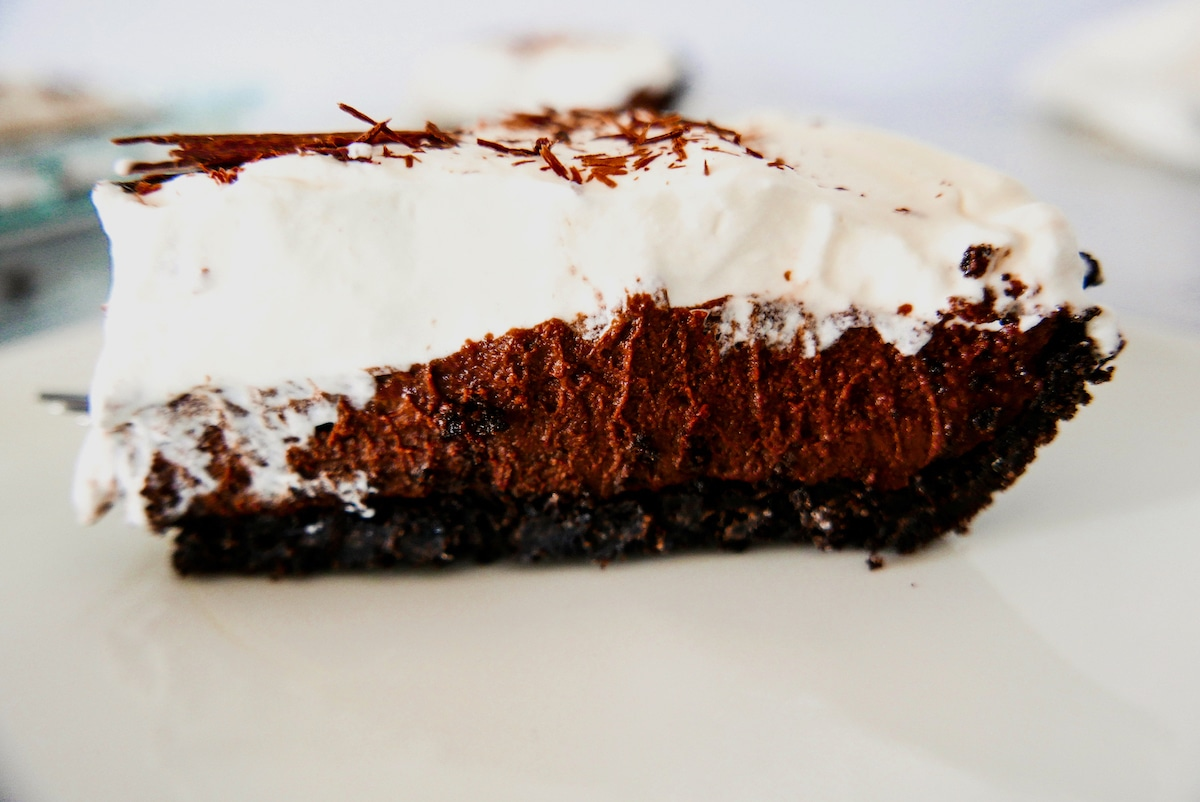 side of one slice of chocolate cream pie on a white plate