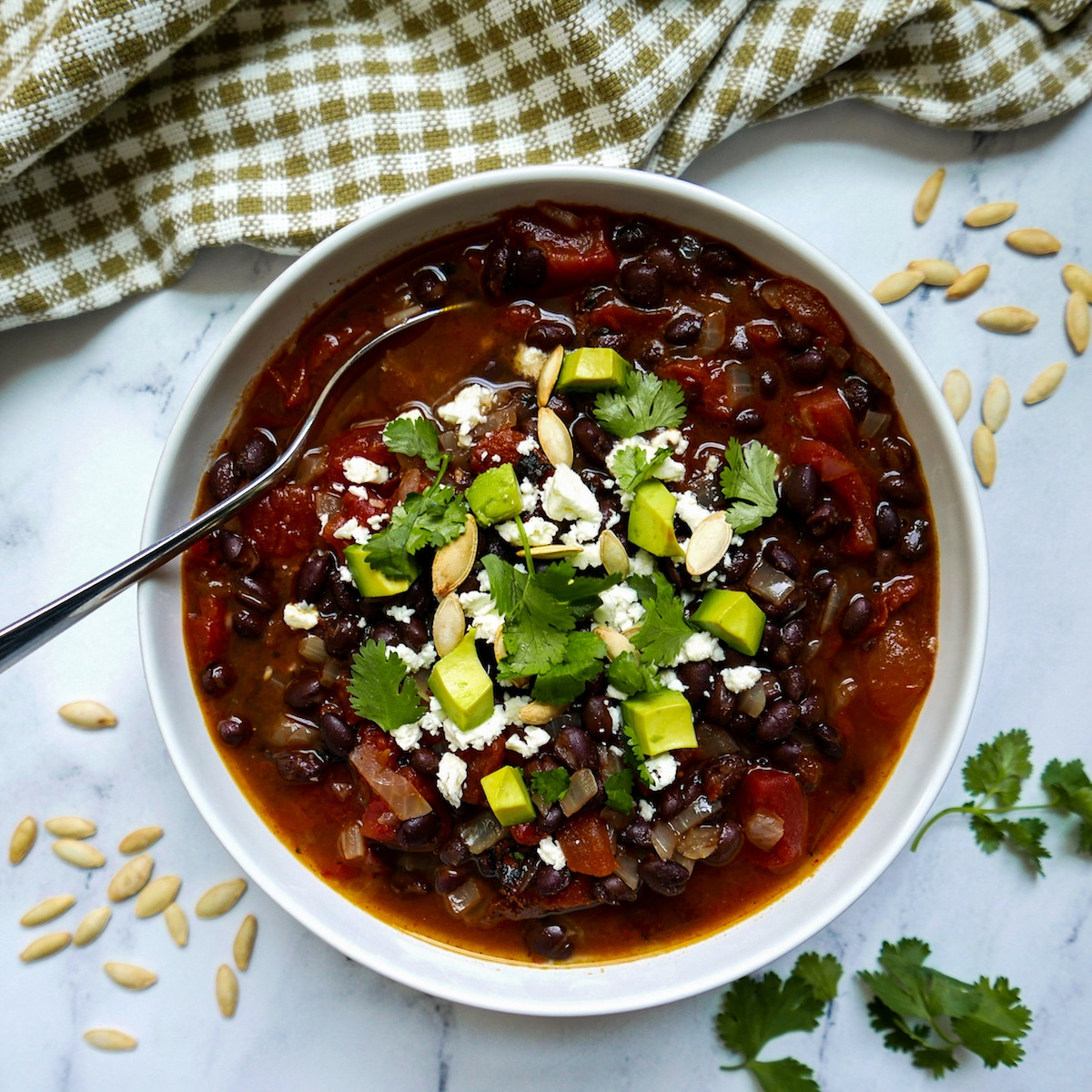 black bean soup in a white bowl garnished with pumpkin seeds and cilantro