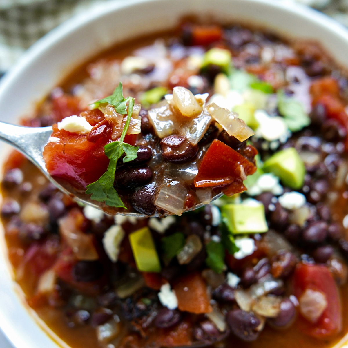 southwest black bean soup with spoon lifting up a bite