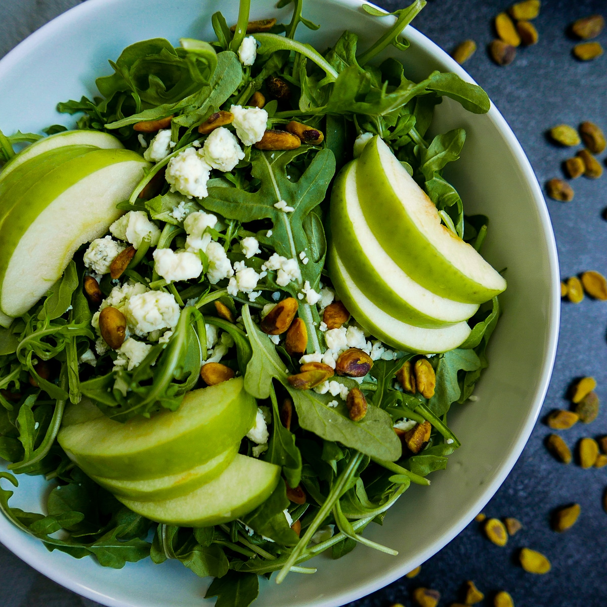 harvest apple salad with pistachios and blue cheese in large white bowl