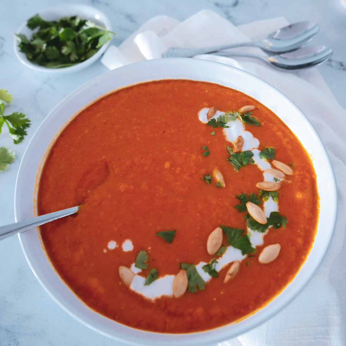 squash carrot ginger soup in bowl with spoon and cilantro