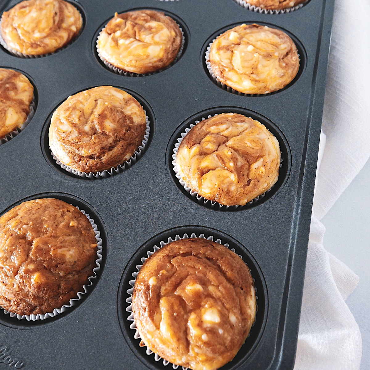 pumpkin cream cheese swirl muffins in baking tin with white dish towel