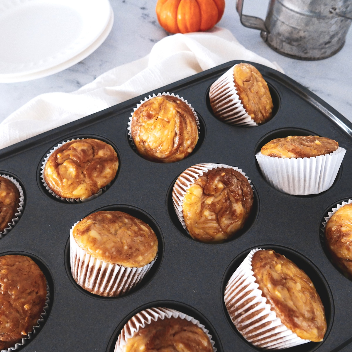 pumpkin cream cheese swirl muffins askew in tin with flour sifter and mini pumpkin in background