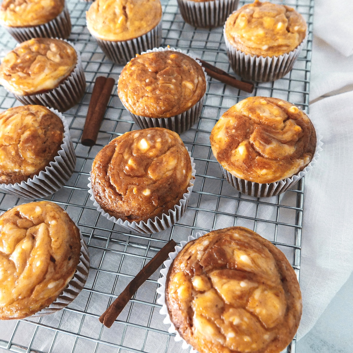 lots of pumpkin cream cheese muffins on wire rack with cinnamon sticks laying nearby