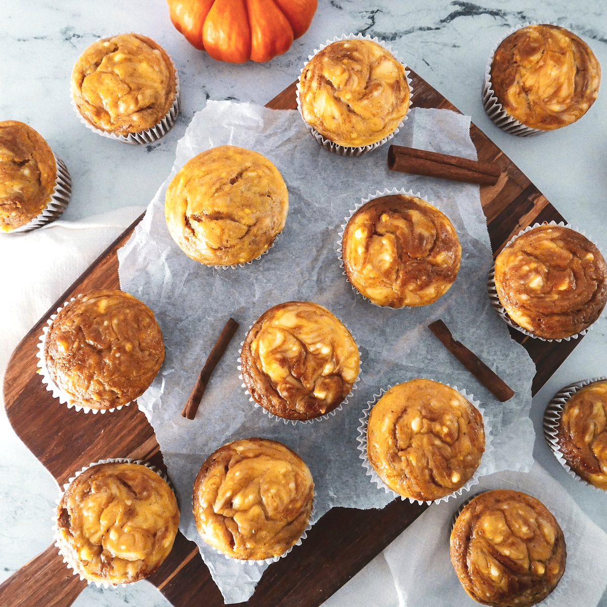 pumpkin cream cheese swirl muffins arranged on a wooden cutting board with parchment, cinnamon sticks, and mini pumpkins