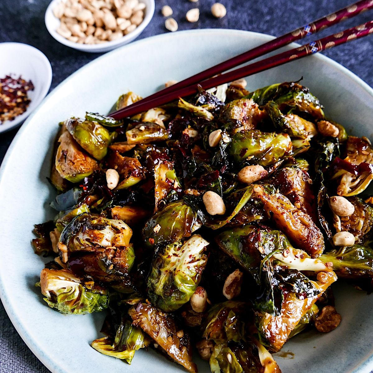 kung pao brussels sprouts garnished with peanuts and chopsticks in a white bowl with cup of peanuts in background