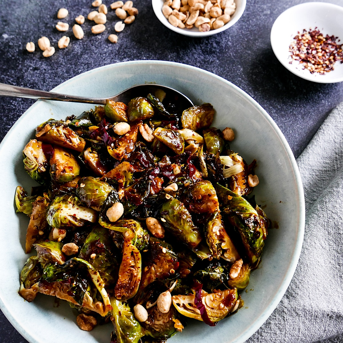 kung pao brussels sprouts in a white bowl with spoon and a cup of peanuts next to bowl