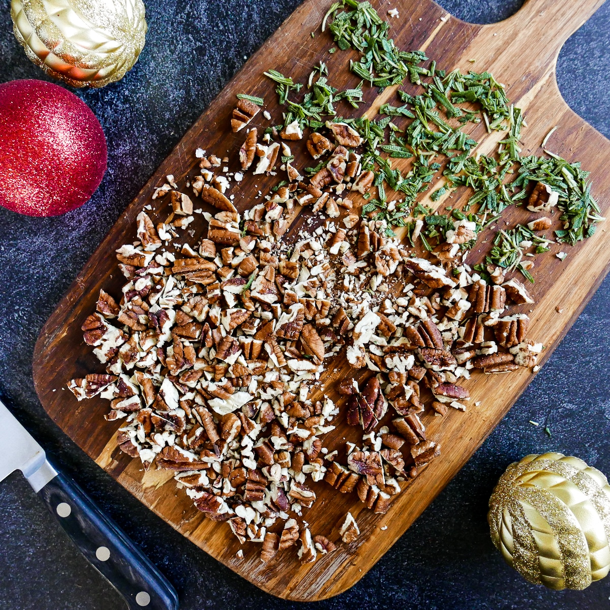 chopped pecans and rosemary on a wooden cutting board with knife
