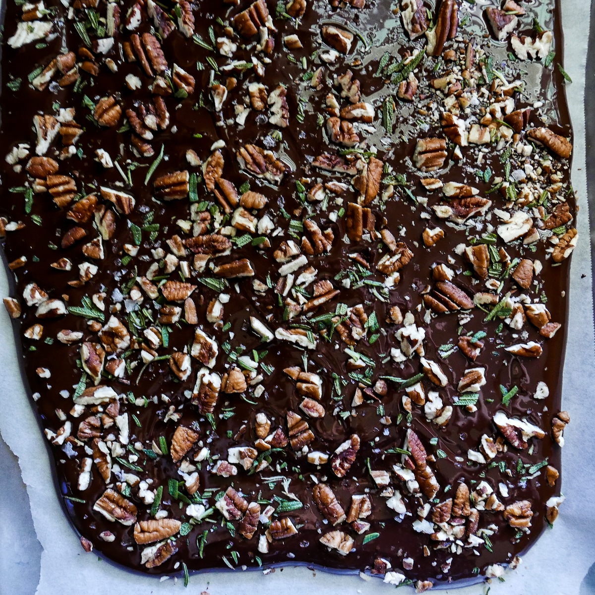 chocolate topped with pecans and rosemary on a baking sheet
