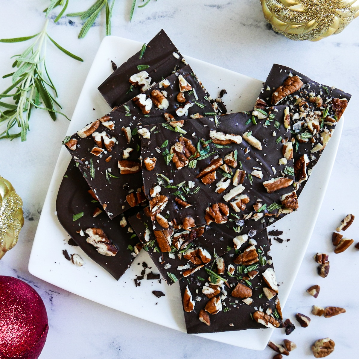 chocolate pecan rosemary bark cut into squares and arranged on a white plate with chopped pecans and rosemary next to plate