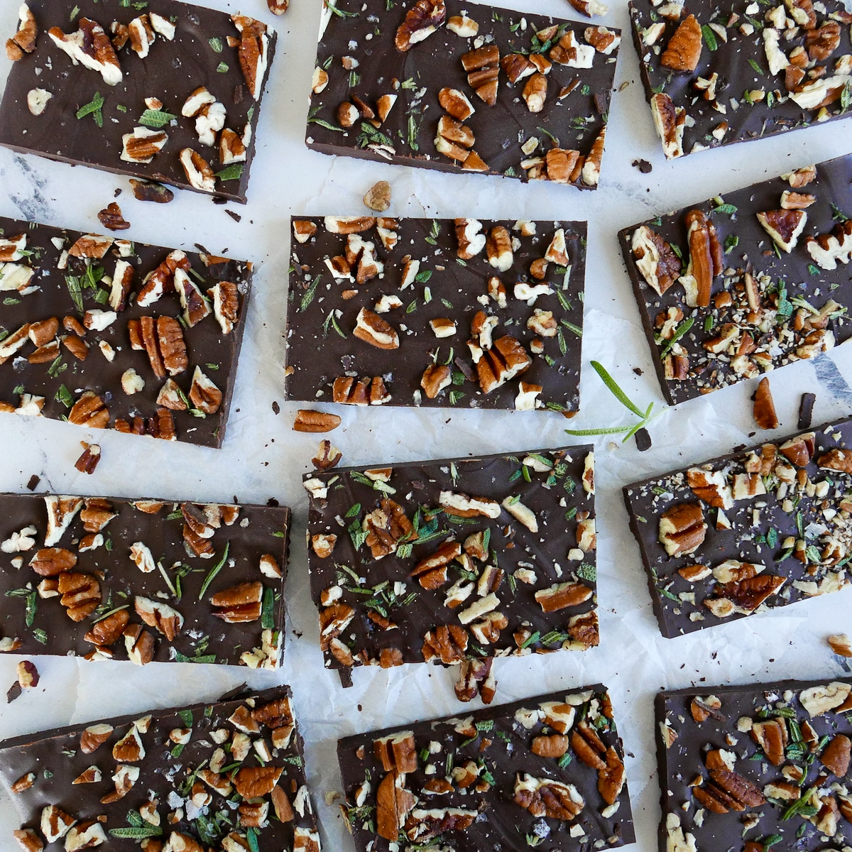 chocolate pecan rosemary bark cut into squares and arranged on parchment