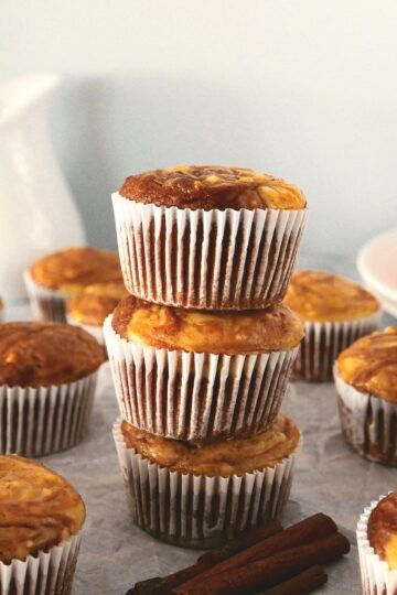 pumpkin cream cheese swirl muffins arranged on a table with milk pitcher in background