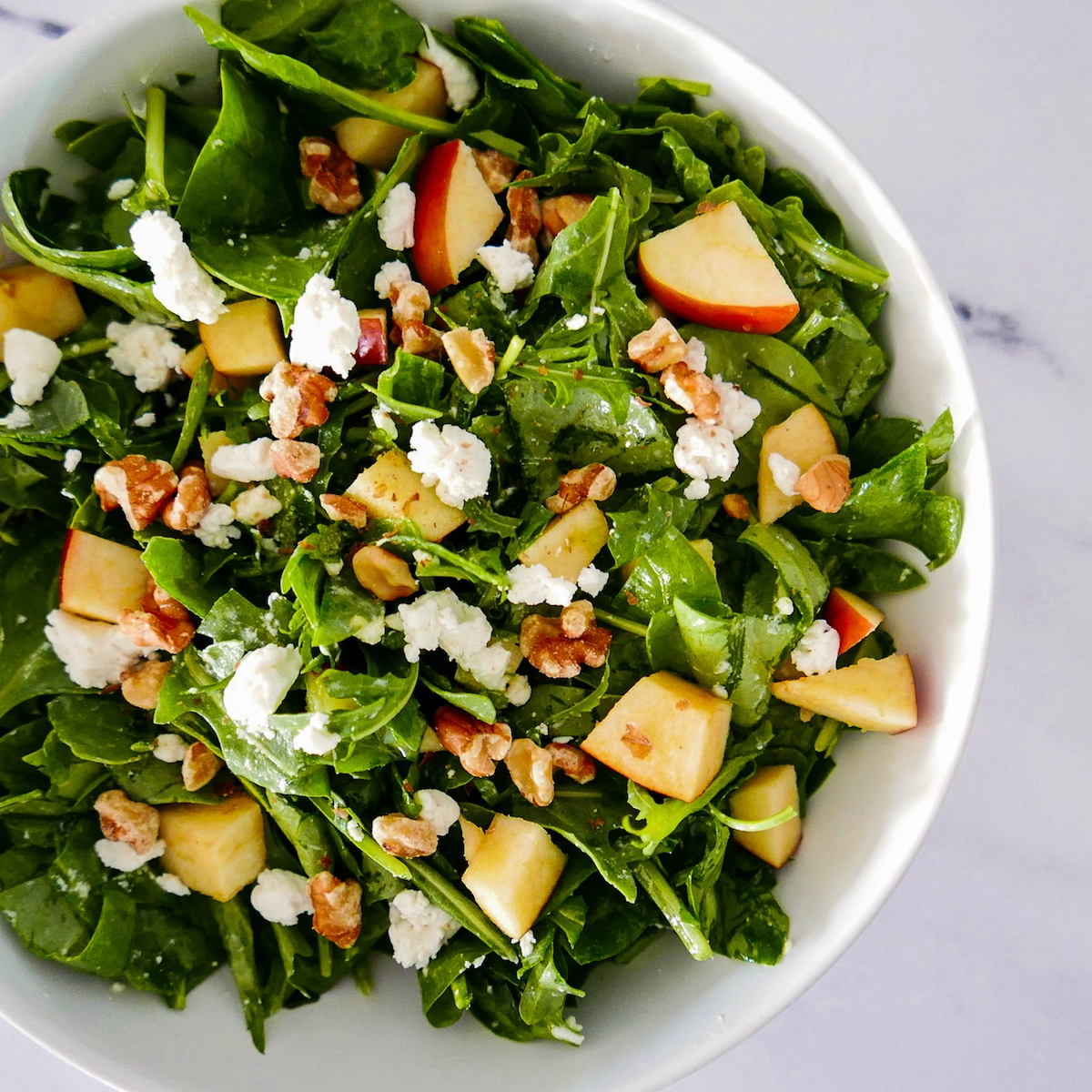apple walnut goat cheese salad in a white bowl