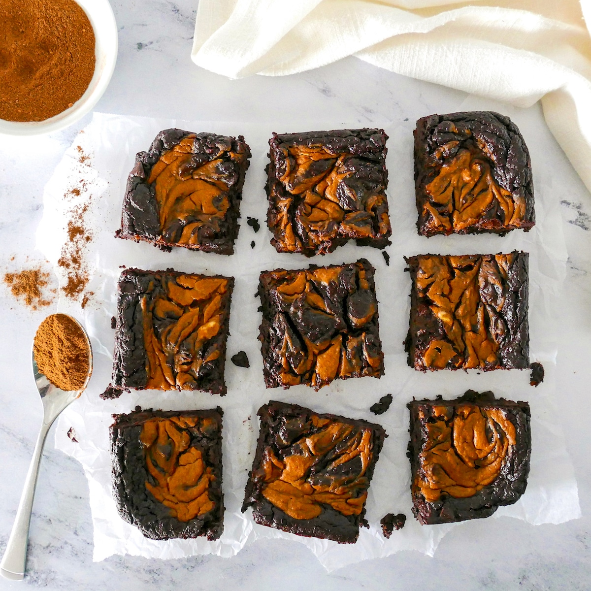 healthy pumpkin brownies cut into nine pieces with cup of cinnamon nearby