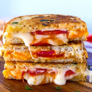 garlic grilled cheese stacked on top of wooden cutting board