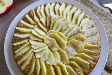dutch apple cake on a white platter with apple halves in background